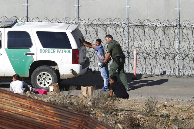 FILE - In this Dec. 15, 2018, file photo, Honduran asylum seekers are taken into custody by U.S. Border Patrol agents after the group crossed the U.S. border wall into San Diego, seen from Tijuana, Mexico. The Trump administration on Monday, June 15, 2020, published sweeping rules making it substantially more difficult to get asylum, moving a step closer to what critics are calling a death blow to the system of seeking humanitarian protection in the United States. (AP Photo/Moises Castillo, File)
