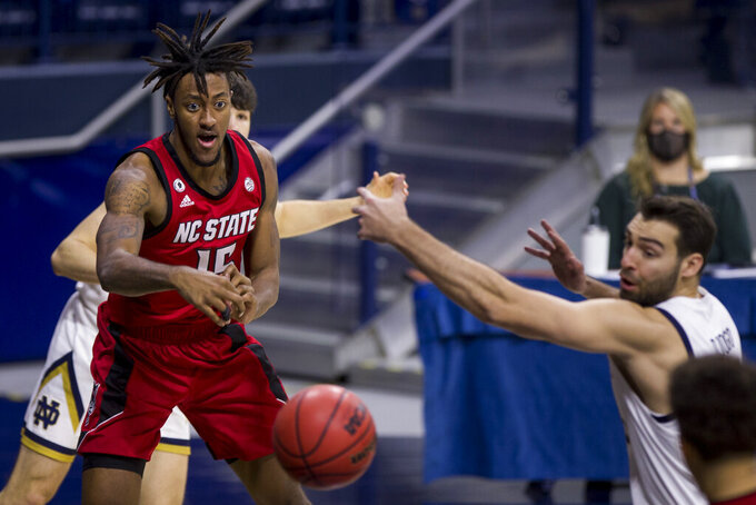 North Carolina State's Manny Bates (15) passes the ball between Notre Dame's Cormac Ryan, left, and Nikola Djogo during the second half of an NCAA college basketball game Wednesday, March 3, 2021, in South Bend, Ind. North Carolina State won 80-69. (AP Photo/Robert Franklin)