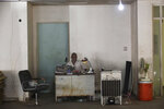 In this Thursday, Dec. 13, 2018 photograph, a man sits behind a desk in the closed Aden Governorate General Hospital in Aden, Yemen. Land mines scattered by Yemen's Houthi rebels will remain a threat even if the latest negotiations succeed in halting the civil war in the Arab world's poorest country. Yemen is also littered with unexploded cluster munitions and bombs dropped by the Saudi-led coalition, including some made in the United States. (AP Photo/Jon Gambrell)