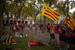 Pro-independence demonstrators rest in a park after taking part at a demonstration during the Catalan National Day in Barcelona, Spain, Saturday, Sept. 11, 2021. Thousands of Catalans have rallied for independence from the rest of Spain in their first major mass gathering since the start of the pandemic. The march in Barcelona on Saturday comes before a meeting between regional leaders in northeast Catalonia and the Spanish government. ( AP Photo/Joan Mateu Parra)