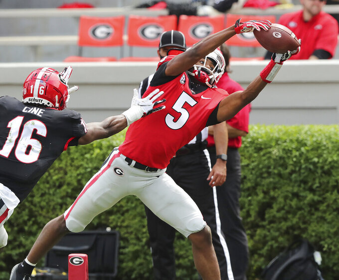 FILE - In this  Saturday, April 17, 2021 file photo, Georgia wide receiver Adonai Mitchell catches a touchdown pass past defensive back Lewis Cine during Georgia's spring NCAA college football game in Athens, Ga. They are young men who are often household names before they've done anything to warrant such attention beyond dominant high school careers. Mitchell.  made a splash with seven catches for 105 yards and a touchdown in Georgia's G-day spring game, and looked fast in the process(Curtis Compton/Atlanta Journal-Constitution via AP, File)