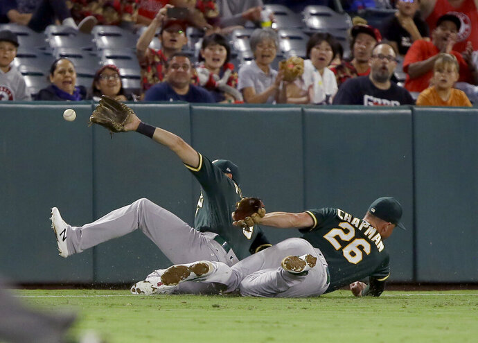 Oakland Athletics left fielder Chad Pinder, left, and third baseman Matt Chapman, right, just miss a fly ball that fell between them for an RBI double by Los Angeles Angels' Brian Goodwin to score Matt Thaiss during the fifth inning of a baseball game in Anaheim, Calif., Tuesday, Sept. 24, 2019. (AP Photo/Alex Gallardo)