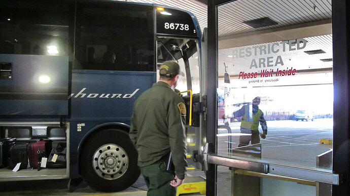 In this Thursday, Feb. 13, 2020 photo, agents for Customs and Border Protection board a Greyhound bus headed for Portland, Ore., at the Spokane Intermodal Center, a terminal for buses and Amtrak in Spokane, Wash. A Customs and Border Protection memo obtained by The Associated Press confirms that bus companies such as Greyhound do not have to allow Border Patrol agents on board to conduct routine checks for illegal immigrants, contrary to Greyhound's long insistence that it has no choice but to let the agents on board. (AP Photo/Nicholas K. Geranios)