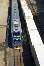 A Missouri River Runner Amtrak train travels alongside a freight train while en route to St. Louis, Friday, June 11, 2021, in Kansas City, Mo. Backers of a proposal to expand passenger rail service through Kansas, Oklahoma and Texas hope the long-discussed package finally has a chance because of an anticipated influx of federal infrastructure funding. (AP Photo/Charlie Riedel)