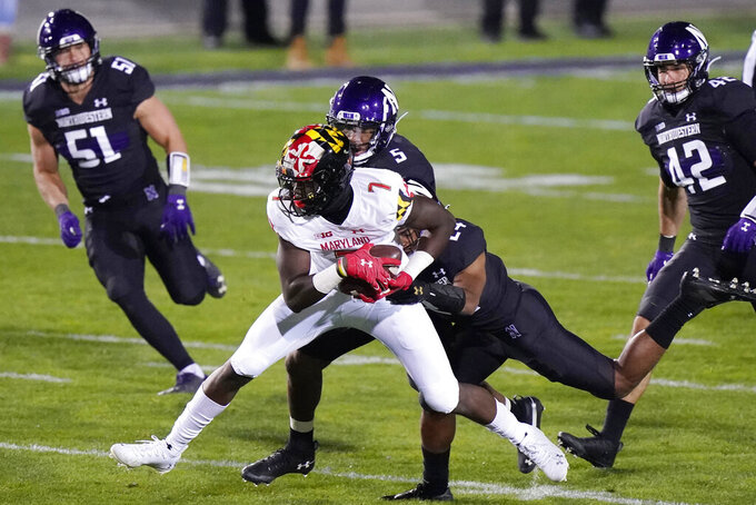 Maryland wide receiver Dontay Demus (7) is tackled by Northwestern defensive back JR Pace (5) and defensive back Rod Heard (24) during the first half of an NCAA college football game in Evanston, Ill., Saturday, Oct. 24, 2020. (AP Photo/Nam Y. Huh)