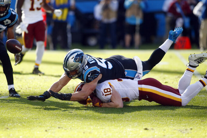 Carolina Panthers middle linebacker Luke Kuechly (59) and Washington Redskins wide receiver Trey Quinn (18) dive for the ball during the first half of an NFL football game in Charlotte, N.C., Sunday, Dec. 1, 2019. (AP Photo/Brian Blanco)