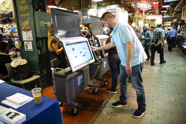 """FILE - In this June 13, 2019, file photo, Steve Marcinkus, an Investigator with the Office of the City Commissioners, demonstrates the ExpressVote XL voting machine at the Reading Terminal Market in Philadelphia. Nearly 1 in 5 U.S. voters will cast ballots this year on devices that look and feel like the discredited paperless voting machines they once used, yet leave a paper record of the vote. Computer security experts are warning that these so-called ballot-marking devices pose too much of a risk. Ballot-marking machines were initially developed not as primary vote-casting tools but as """"accessible"""" alternatives for the disabled. They print out paper records that are scanned by optical readers that tabulate the vote. They cost at least twice as much as hand-marked paper ballots, which computer scientists prefer because paper can't be hacked.(AP Photo/Matt Rourke, File)"""