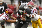 Southern California cornerback Jayden Williams and safety Xavion Alford tackle Washington State wide receiver Calvin Jackson Jr. during the first half of an NCAA college football game, Saturday, Sept. 18, 2021, in Pullman, Wash. (AP Photo/Young Kwak)