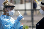 FILE - In this Aug. 13, 2020, file photo, nurse practitioner Debbi Hinderliter, left, collects a sample from a woman at a coronavirus testing site near the nation's busiest pedestrian border crossing in San Diego. U.S. health officials have sparked a wave of confusion after posting guidelines that coronavirus testing is not necessary for people who have been in close contact with infected people. (AP Photo/Gregory Bull, File)