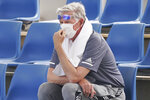 A spectator wears a mask as smoke haze shrouds Melbourne during an Australian Open practice session at Melbourne Park in Australia, Tuesday, Jan. 14, 2020. Smoke haze and poor air quality caused by wildfires temporarily suspended practice sessions for the Australian Open at Melbourne Park on Tuesday, but qualifying began later in the morning in