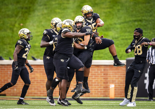 Wake Forest defensive back Nick Andersen (45) is congratulated by teammates after intercepting a pass in the end zone on the last play of the first half of an NCAA college football game against Virginia Tech, Saturday, Oct. 24, 2020, in Winston-Salem, N.C. (Andrew Dye/The Winston-Salem Journal via AP)