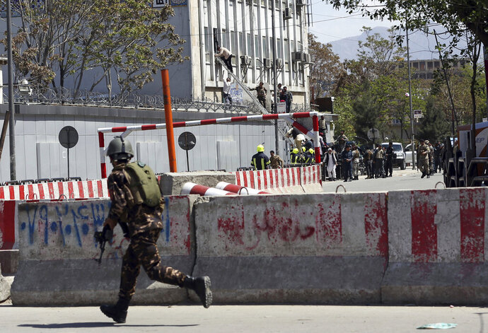 An Afghan Security personnel arrives on the perimeter outside the Telecommunication Ministry during a gunfight with insurgents in Kabul, Afghanistan, Saturday, April 20, 2019. Afghan officials say an explosion has rocked the telecommunications ministry in the capital city of Kabul. Nasart Rahimi, a spokesman for the interior ministry, said Saturday the blast occurred during a shootout with security forces. (AP Photo/Rahmat Gul)