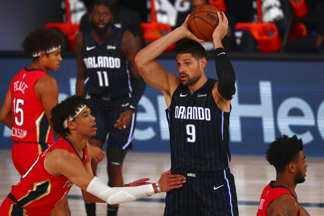 Orlando Magic center Nikola Vucevic (9) controls the ball against New Orleans Pelicans center Jaxson Hayes, front left, during the first half of an NBA basketball game Thursday, Aug. 13, 2020, in Lake Buena Vista, Fla. (Kim Klement/Pool Photo via AP)