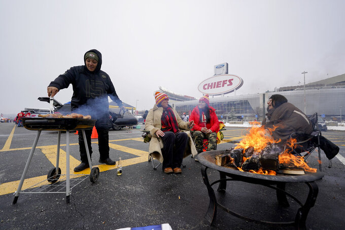 Fans tailgate in the parking lot outside Arrowhead Stadium before an NFL football game between the Los Angeles Chargers and the Kansas City Chiefs, Sunday, Jan. 3, 2021, in Kansas City, Mo. (AP Photo/Charlie Riedel)