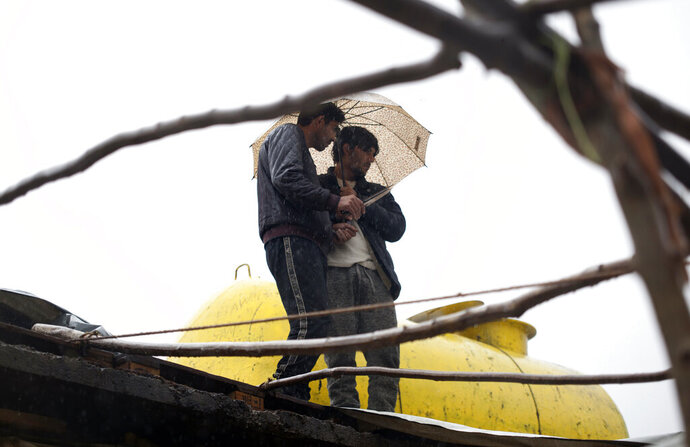 Migrants stand with an umbrella in the Vucjak refugee camp outside Bihac, northwestern Bosnia, Saturday, Nov. 16, 2019. A storm in Bosnia has swept through the bleak make-shift camp, blowing many migrant's tents away. (AP Photo/Almir Alic)