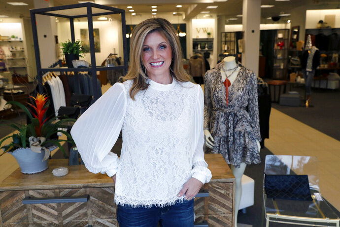 In this Tuesday, Nov. 26, 2019, photo Amy Witt, owner of the Velvet Window, posses for a photo at her retail store in Dallas. Heading into the holiday shopping season, Witt opened a physical store last week to attract more shoppers than just those who have been her online customers. (AP Photo/LM Otero)