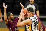 Iowa center Luka Garza (55) drives around North Carolina Central guard Nicolas Fennell, left, during the first half of an NCAA college basketball game, Wednesday, Nov. 25, 2020, in Iowa City, Iowa. (AP Photo/Charlie Neibergall)