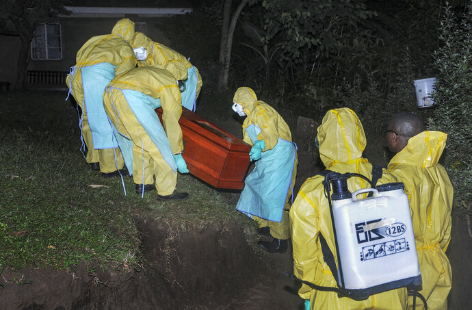 Workers wearing protective clothing bury Agnes Mbambu who died of Ebola, the 50-year-old grandmother of the 5-year-old boy who became Ebola's first cross-border victim, in the village of Karambi, near the border with Congo, in western Uganda Thursday, June 13, 2019. The two were part of a larger Congolese-Ugandan family who crossed to Congo when one of their elders there, a pastor, became sick with Ebola and they crossed back into Uganda on June 9 via a footpath not patrolled by border authorities. (AP Photo/Ronald Kabuubi)