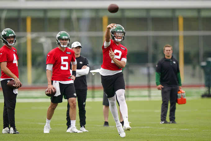 New York Jets backup quarterbacks James Morgan (4) and Mike White (5) watch quarterback Zach Wilson (2) throw a pass during an NFL football practice, Wednesday, June 2, 2021, in Florham Park, N.J. (AP Photo/Kathy Willens)