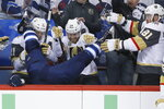 Winnipeg Jets' Blake Wheeler gets dumped over the boards by Vegas Golden Knights' Ryan Reaves, not seen, in front of Cody Eakin (21), Oscar Lindberg (24) and Jonathan Marchessault (81) during the first period of Game 1 of the NHL hockey playoffs Western Conference final, Saturday, May 12, 2108, in Winnipeg, Manitoba. (John Woods/The Canadian Press via AP)