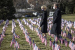 Kentucky Gov. Andy Beshear and his wife, First Lady Britainy Beshear, look at the more than 3,000 flags on the lawn at the state Capitol in Frankfort, Ky., Friday, Jan. 22, 2021. Each flag memorializes a Kentuckian who died from complications from COVID-19.   (Ryan C. Hermens/Lexington Herald-Leader via AP)