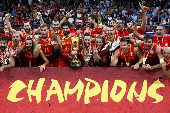 Members of Spain's team celebrate with the Naismith Trophy after they beat Argentina in their first-place match in the FIBA Basketball World Cup at the Cadillac Arena in Beijing, Sunday, Sept. 15, 2019. (AP Photo/Mark Schiefelbein)