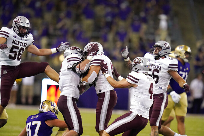 Montana's Marcus Welnel, center, is surrounded by teammates after intercepting against Washington late in the second half of an NCAA college football game Saturday, Sept. 4, 2021, in Seattle. Montana won 13-7. (AP Photo/Elaine Thompson)