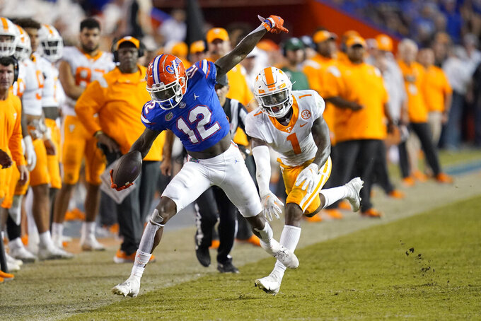 Florida wide receiver Rick Wells (12) is forced out of bounds by Tennessee defensive back Trevon Flowers (1) after a reception during the second half of an NCAA college football game, Saturday, Sept. 25, 2021, in Gainesville, Fla. (AP Photo/John Raoux)