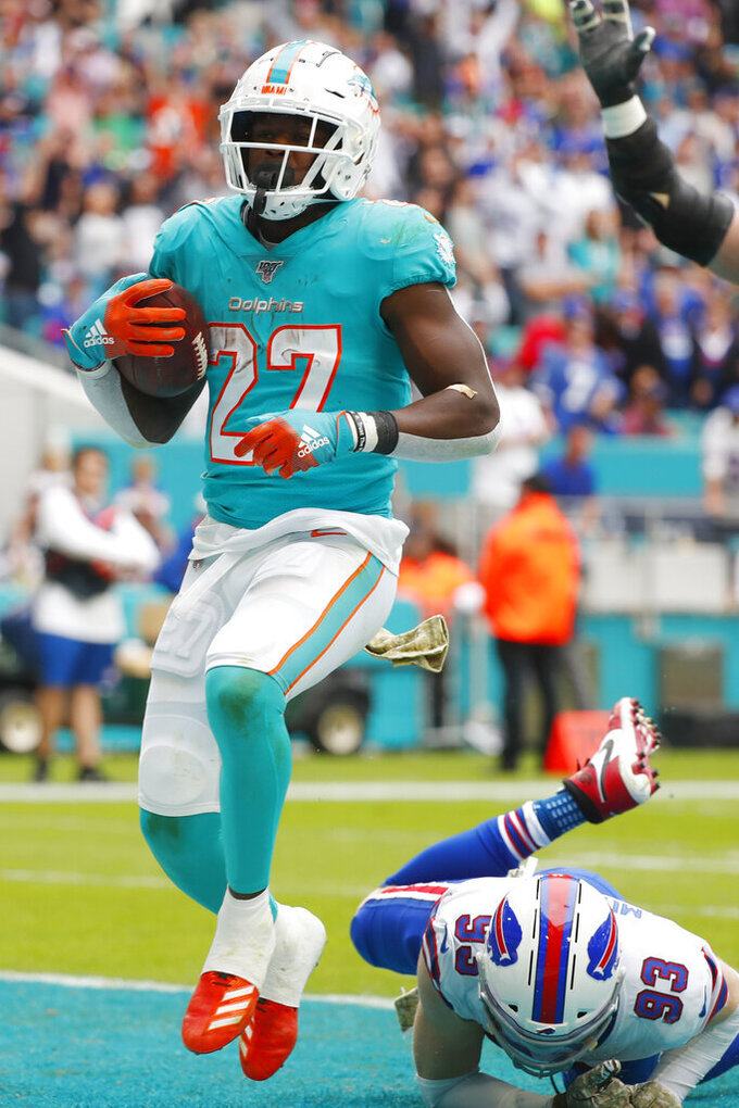 Miami Dolphins running back Kalen Ballage (27) scores a touchdown ahead of a tackle by Buffalo Bills defensive end Trent Murphy (93), during the first half at an NFL football game, Sunday, Nov. 17, 2019, in Miami Gardens, Fla. (AP Photo/Wilfredo Lee)