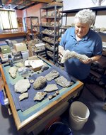 In this Aug. 6, 2019, photo, Robert Wolf, of Fort Dodge, Iowa, holds the fossilized remains of a path or burrow made by an unknown ancient animal that he's going to keep. Wolf has donated most of his collection of fossils and books to the University of Iowa, The University of Northern Iowa and the University of Pittsburgh. (Hans Madsen /The Messenger via AP)