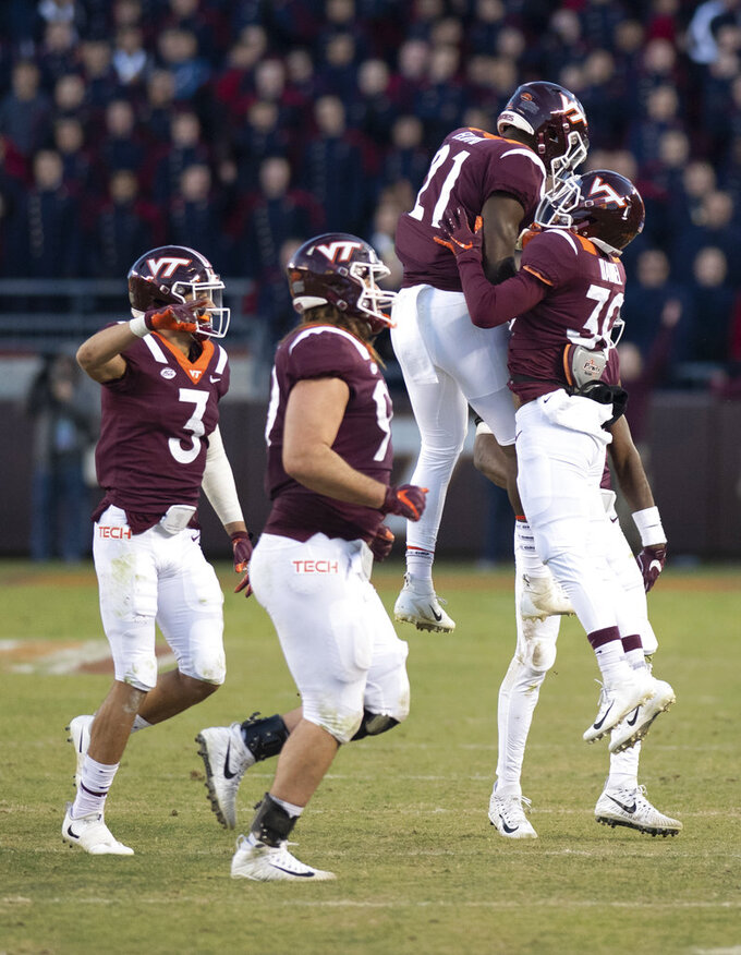 Virginia Tech celebrates a turnover on downs that was overturned after review during an NCAA college football game against Boston College in Blacksburg, Va., Saturday, Nov. 3, 2018. (AP Photo/Matt Bell)