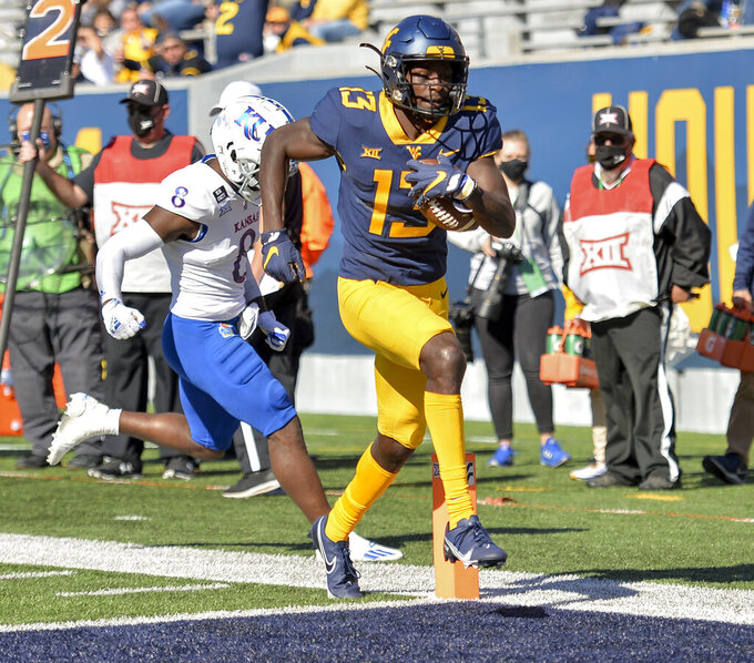 West Virginia wide receiver Sam James (13) scores a touchdown against Kansas during an NCAA college football game, Saturday, Oct. 17, 2020, in Morgantown, W.Va. (William Wotring/The Dominion-Post via AP)