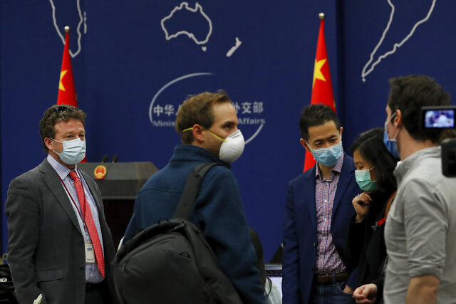 The New York Times Beijing based correspondent Steven Lee Myers, left, chats with other foreign journalists after attending a daily briefing by Chinese Foreign Ministry spokesman Geng Shuang at the Ministry of Foreign Affairs office in Beijing, Wednesday, March 18, 2020. At least 13 American journalists stand to be expelled from China in retaliation for a new limit imposed by the Trump administration on visas for Chinese state-owned media operating in the U.S. (AP Photo/Andy Wong)