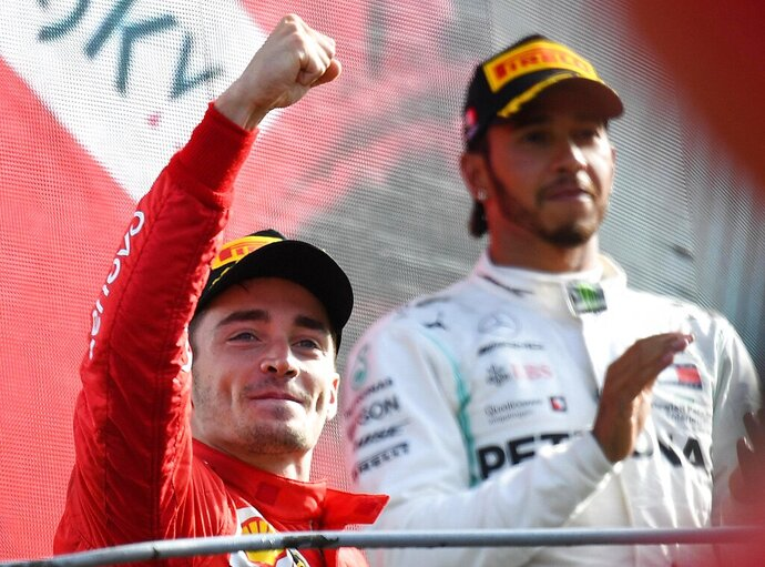 Ferrari driver Charles Leclerc of Monaco, left, celebrates with third placed Mercedes driver Lewis Hamilton of Britain, on podium after winning the Formula One Italy Grand Prix at the Monza racetrack, in Monza, Italy, Sunday, Sept.8, 2019. (AP Photo/Antonio Calanni) (Daniel Dal Zennaro/ANSA Via AP)