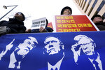 Protesters hold a banner showing images, from left, of U.S. President Donald Trump, Secretary of State Mike Pompeo and National Security Adviser John Bolton during a rally against the United States' policy to put steady pressure on North Korea, near the U.S. Embassy in Seoul, South Korea, Friday, March 22, 2019. The Trump administration on Thursday sanctioned two Chinese shipping companies suspected of helping North Korea evade sanctions, the first targeted actions taken against Pyongyang since its nuclear negotiations with the U.S. in Hanoi last month ended without agreement. The signs read: