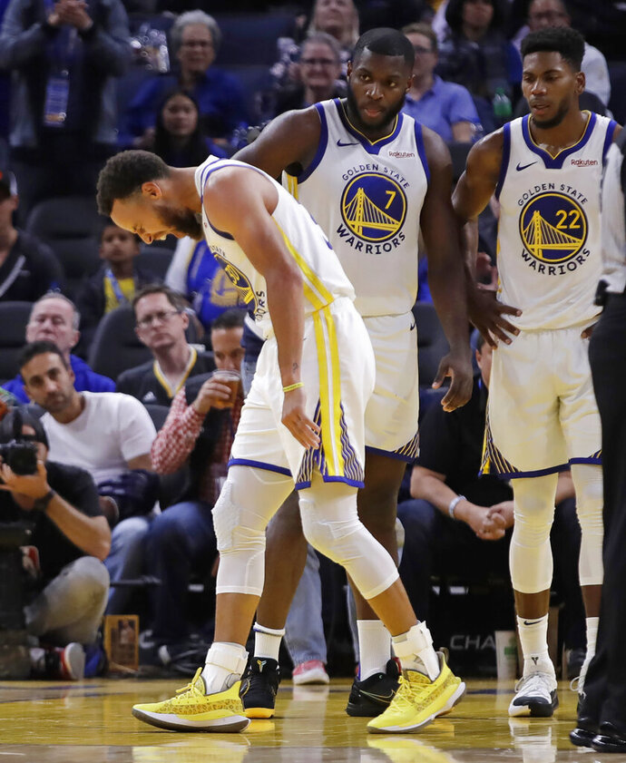Golden State Warriors' Stephen Curry, left, grimaces as Eric Paschall (7) and Glenn Robinson III (22) watch, after Phoenix Suns' Aron Baynes fell onto Curry during the second half of an NBA basketball game Wednesday, Oct. 30, 2019, in San Francisco. Curry left the game. (AP Photo/Ben Margot)