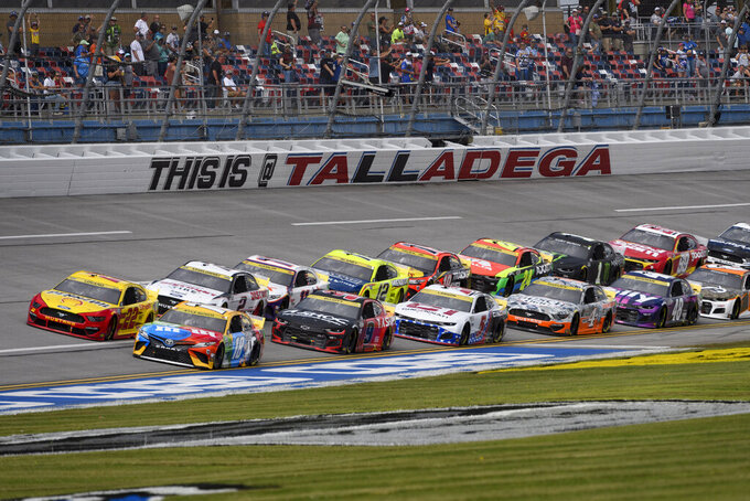 Kyle Busch (18) and Joey Logano (22) run in front during a NASCAR Cup series auto race Monday, Oct. 4, 2021, in Talladega, Ala. (AP Photo/John Amis)