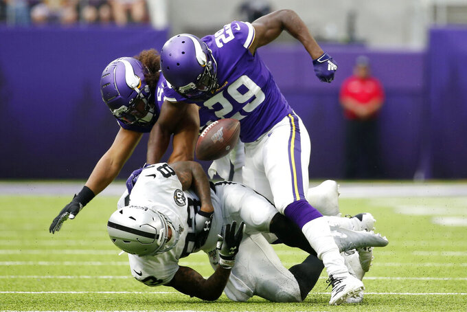 Oakland Raiders tight end Darren Waller fumbles after getting hit by Minnesota Vikings defenders Xavier Rhodes (29) and Eric Kendricks, rear, during the second half of an NFL football game, Sunday, Sept. 22, 2019, in Minneapolis. (AP Photo/Bruce Kluckhohn)