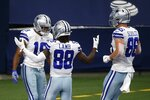 Dallas Cowboys' Amari Cooper, left, CeeDee Lamb (88) and Dalton Schultz (86) celebrate after Cooper caught a touchdown pass in the first half of an NFL football game against the Cleveland Browns in Arlington, Texas, Sunday, Oct. 4, 2020. (AP Photo/Michael Ainsworth)