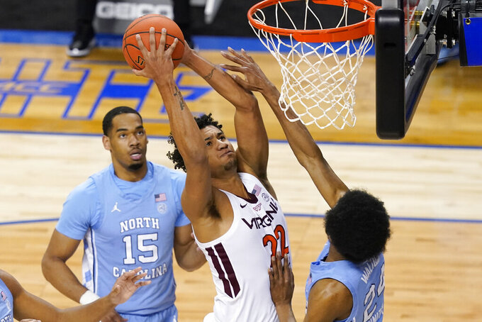 Virginia Tech forward Keve Aluma (22) goes up for a shot as North Carolina guard Kerwin Walton (24) and North Carolina forward Garrison Brooks (15) defend during the first half of an NCAA college basketball game in the quarterfinal round of the Atlantic Coast Conference tournament in Greensboro, N.C., Thursday, March 11, 2021. (AP Photo/Gerry Broome)