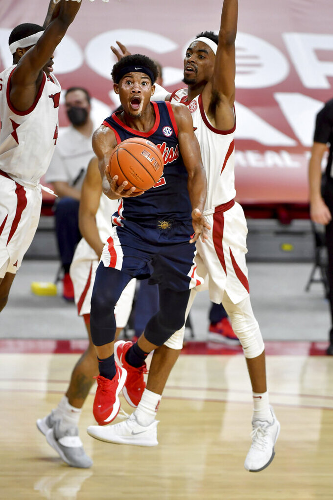 Mississippi guard Devontae Shuler (2) drives past Arkansas defender Jalen Tate (11) during the second half of an NCAA college basketball game Wednesday, Jan. 27, 2021, in Fayetteville, Ark. (AP Photo/Michael Woods)