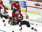 New Jersey Devils right wing Kyle Palmieri (21) scores on Ottawa Senators goaltender Marcus Hogberg (35) as Senators defenseman Mike Reilly (5) and Devils left wing Jesper Bratt (63) look on during third period NHL hockey action in Ottawa on Monday, Jan. 27, 2020. (Fred Chartrand/The Canadian Press via AP)