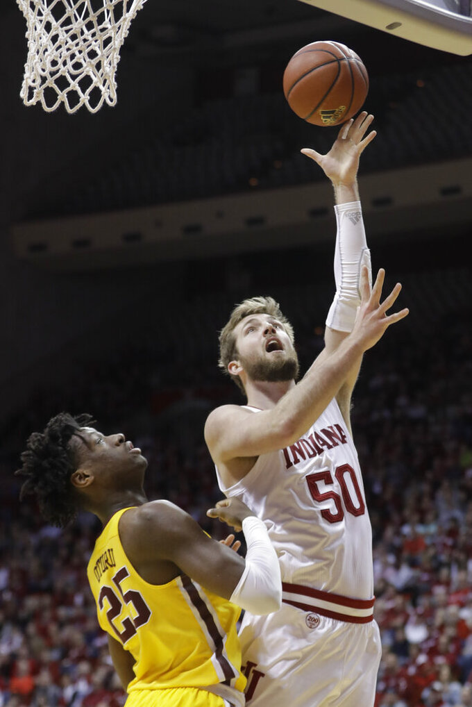 Indiana's Joey Brunk (50) shoots over Minnesota's Daniel Oturu (25) during the first half of an NCAA college basketball game Wednesday, March 4, 2020, in Bloomington, Ind. (AP Photo/Darron Cummings)