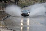 A car hits a deep section of rain run off along Peach Avenue in Hesperia, Calif., Thursday, Jan. 17, 2019. (James Quigg/The Daily Press via AP)