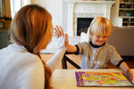 "In this Wednesday, March 27, 2019, photo, Kacey Ruegsegger Johnson high-fives with her son Corban as they finish a puzzle in their Cary, N.C., home. Twenty years after teenage gunmen attacked Columbine High School, Ruegsegger Johnson and other alumni of the Littleton, Colo., school have become parents. ""I'm grateful I have the chance to be a mom. I know some of my classmates weren't given that opportunity,"" Ruegsegger Johnson said, tears springing to her eyes. (AP Photo/Allen G. Breed)"