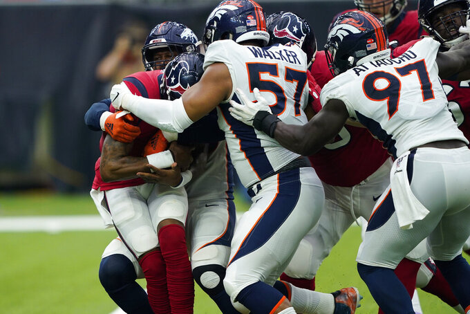 Houston Texans quarterback Deshaun Watson, left, is swarmed by Denver Broncos defenders during the first half of an NFL football game Sunday, Dec. 8, 2019, in Houston. (AP Photo/David J. Phillip)