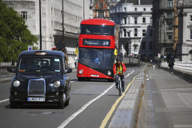 A cyclist rides his bike along Waterloo Bridge, in London, Monday, May 18, 2020. Large areas of London are to be closed to cars and vans to allow people to walk and cycle safely as the coronavirus lockdown is eased, including Waterloo Bridge and London Bridge. (AP Photo/Alberto Pezzali)