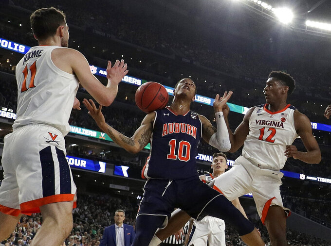 Auburn's Samir Doughty (10) battles for a rebound against Virginia's Ty Jerome (11) and De'Andre Hunter (12) during the first half in the semifinals of the Final Four NCAA college basketball tournament, Saturday, April 6, 2019, in Minneapolis. (AP Photo/David J. Phillip)