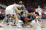 Duke guard Tre Jones (3) falls to the floor chasing the ball with North Carolina State forward Danny Dixon, left, during the first half of an NCAA college basketball game in Raleigh, N.C., Wednesday, Feb. 19, 2020. (AP Photo/Gerry Broome)
