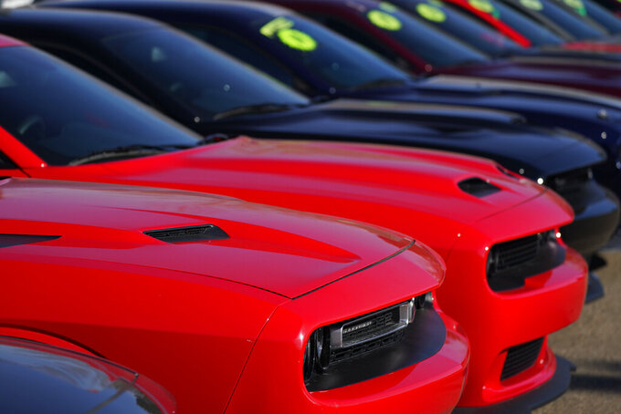 This Jan. 24, 2021 photo shows a long line of used Challengers at a Dodge dealership in Littleton, Colo.   In 2021,  high demand and low supply have driven up used vehicle prices so much that many are now selling for more than their original sticker price when they were new.   (AP Photo/David Zalubowski)